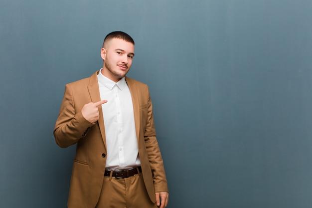 Młody przystojny biznesmen patrzeje dumny, ufny i szczęśliwy, ono uśmiecha się i wskazuje jaźń lub robi liczbie jeden znakowi przeciw płaskiej ścianie