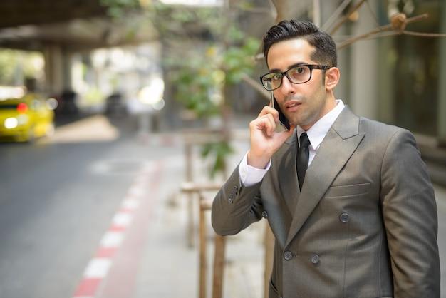 Młody przystojny biznesmen perski czeka podczas rozmowy przez telefon na ulicach miasta na świeżym powietrzu