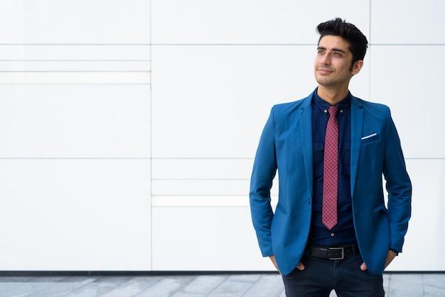 Młody przystojny biznesmen perski pozowanie przed białą ścianą