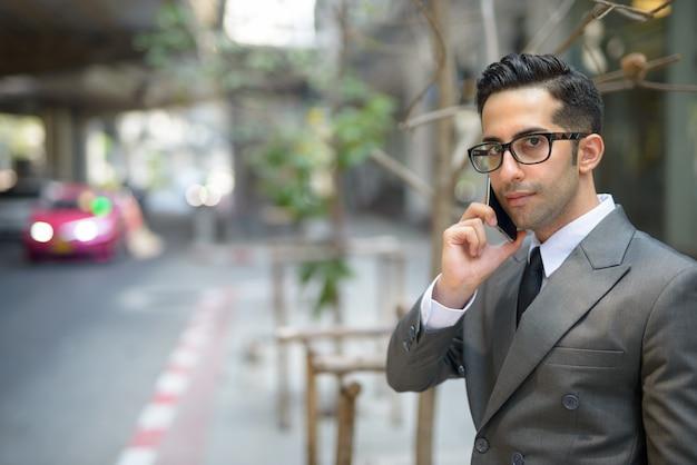 Młody przystojny biznesmen perski rozmawia przez telefon na ulicach miasta na świeżym powietrzu