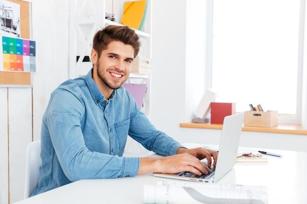 Młody przystojny biznesmen, pisząc na laptopie i patrząc na kamerę, siedząc w biurze
