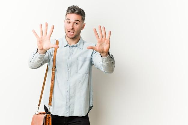Młody przystojny biznesmen pokazuje numer dziesięć rękami.