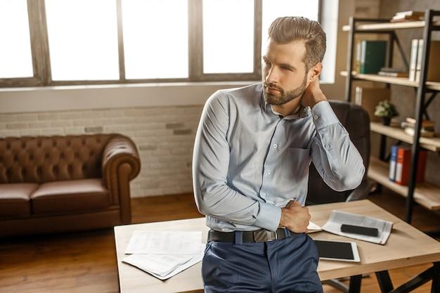 Młody przystojny biznesmen pozuje w jego swój biurze. staje przy stole i obejmuje się. facet patrzy w bok. telefon i tablet z notebookiem na stole za.