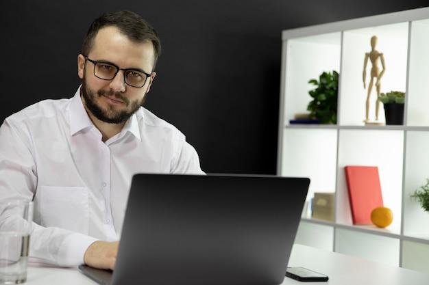 Młody przystojny biznesmen pracuje przy komputerem w ministerstwie spraw wewnętrznych. uśmiechnięty freelancer