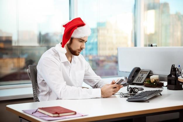 Młody przystojny biznesmen pracuje w biurze na święto bożęgo narodzenia.