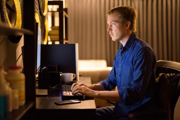 Młody przystojny biznesmen pracy w godzinach nadliczbowych w domu późno w nocy