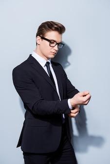 Młody przystojny biznesmen prawnik w garniturze naprawia swoje tusze do mankietów, stoi na czystej przestrzeni światła. taki dojrzały i męski, gorący i pewny siebie