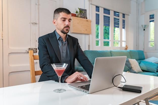 Młody przystojny biznesmen przy drinku podczas rozmowy wideo online