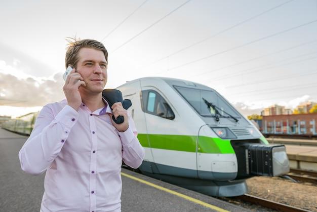 Młody przystojny biznesmen rozmawia przez telefon komórkowy przed pociągiem na stacji kolejowej