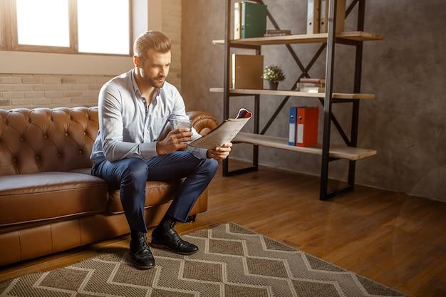 Młody przystojny biznesmen siedzi na kanapie i czyta dziennik w swoim własnym biurze. trzyma w ręce kieliszek whisky. ufny i seksowny młodego człowieka pozować.