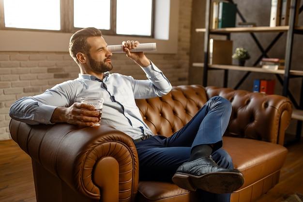 Młody przystojny biznesmen siedzieć na kanapie i grać w swoim biurze. patrzy prosto przez zwinięty dziennik. facet trzymać szklankę z whisky w ręku. noga na innym. pewność siebie.