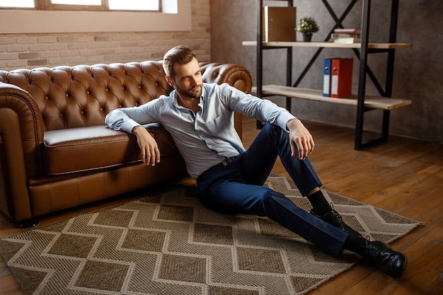 Młody przystojny biznesmen siedzieć na podłodze i pozować w swoim własnym biurze. patrzy prosto z pewnością. seksowny młody człowiek opiera się na kanapie.