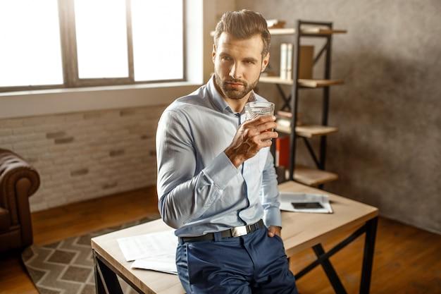 Młody przystojny biznesmen stać i trzymać kieliszek whisky w swoim własnym biurze. patrzy w bok i pochyla się do stołu. światło dzienne.