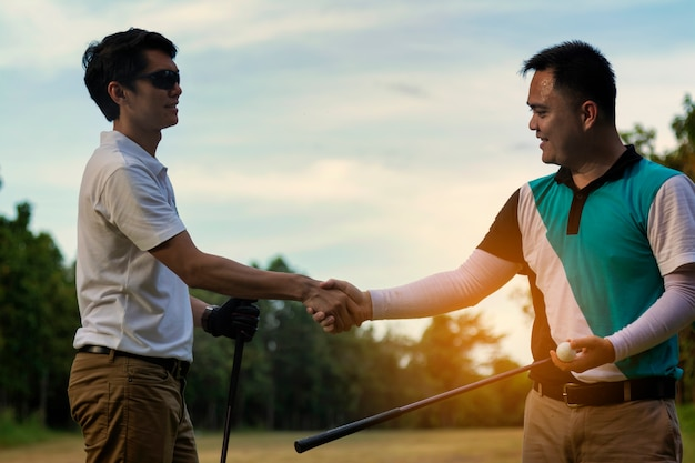 Młody przystojny biznesmen trząść ręki na golfie