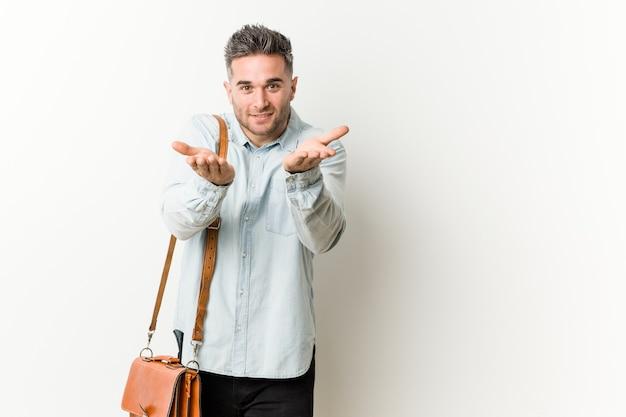 Młody przystojny biznesmen trzyma coś z palmami, oferując aparat.