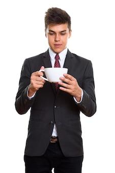 Młody przystojny biznesmen trzymając filiżankę kawy i patrząc na nią
