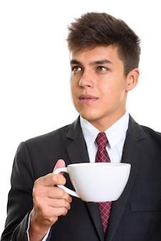 Młody przystojny biznesmen trzymając filiżankę kawy podczas myślenia