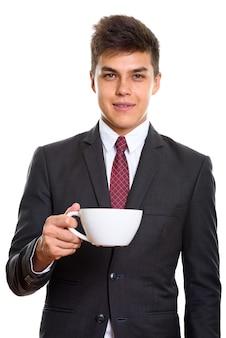 Młody przystojny biznesmen trzymając filiżankę kawy