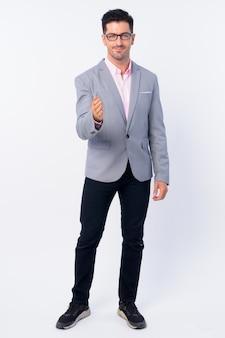 Młody przystojny biznesmen ubrany w garnitur na białym tle białej ścianie