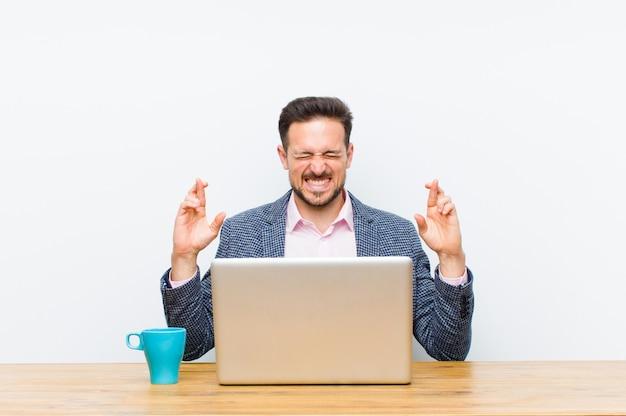 Młody przystojny biznesmen uśmiecha się i niespokojnie przekraczając oba palce