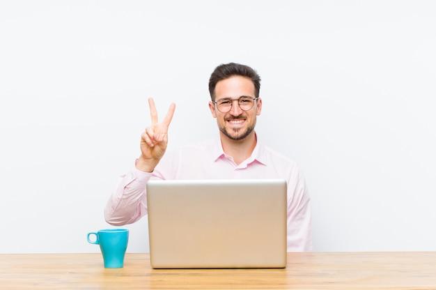 Młody przystojny biznesmen uśmiecha się i szuka przyjazny, pokazując numer dwa lub drugi
