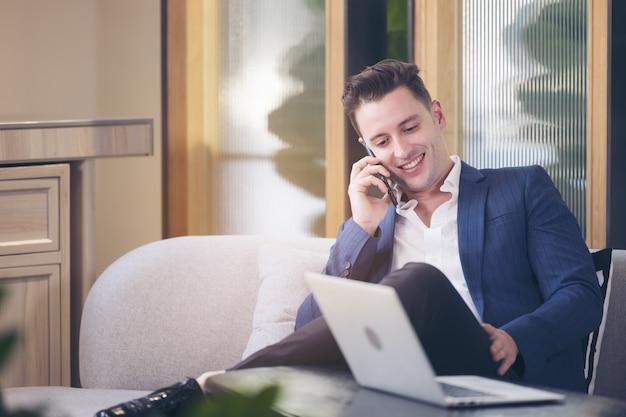 Młody przystojny biznesmen uśmiecha się rozmawia przez telefon, siedząc przy stole w kawiarni