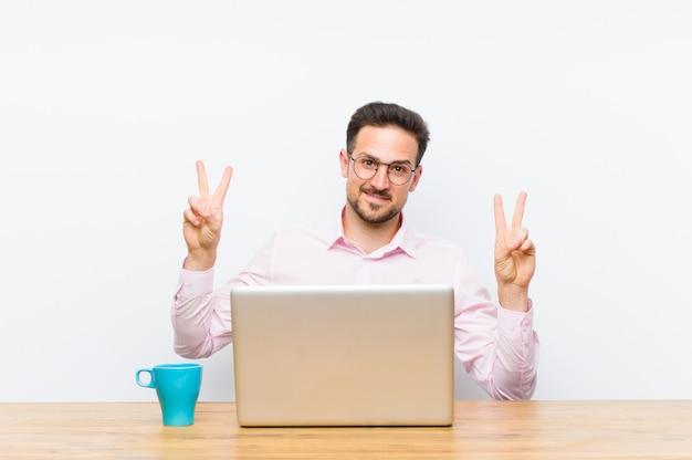 Młody przystojny biznesmen uśmiechnięty i patrząc szczęśliwy, przyjazny i zadowolony, gestem zwycięstwa lub pokoju obiema rękami