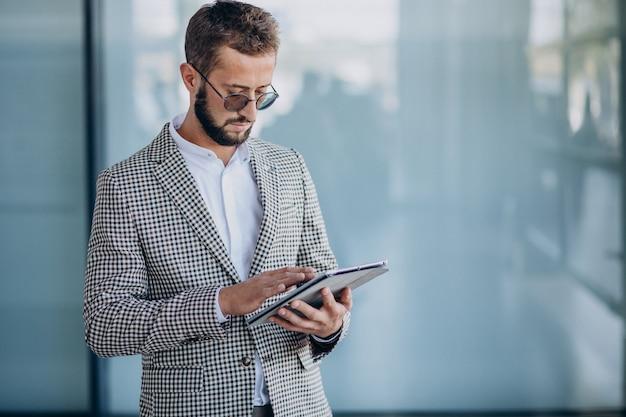 Młody przystojny biznesmen w biurze trzymając tabletkę