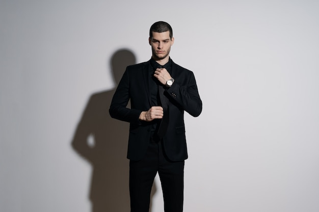 Młody przystojny biznesmen w czarnej koszuli i czarnym garniturze
