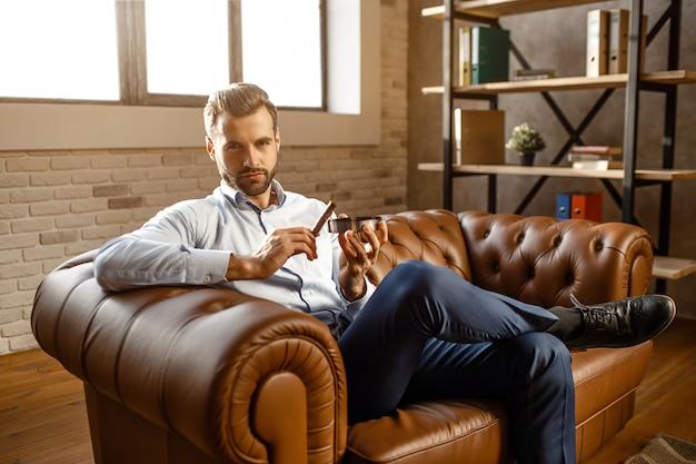 Młody przystojny biznesmen w dymnym cygarze jego własny biuro. siada na kanapie i trzyma go popielnikiem. facet z ufnością patrzy w kamerę. brutalny i seksowny.