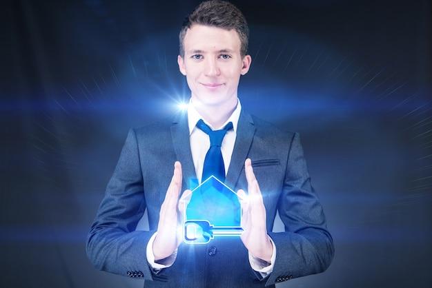Młody przystojny biznesmen w hipotecznym pojęciu