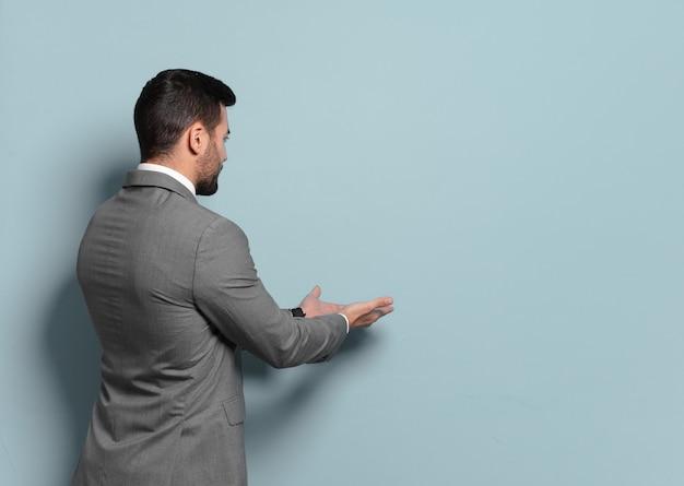 Młody przystojny biznesmen wskazujący lub pokazujący puste miejsce do koncepcji yout