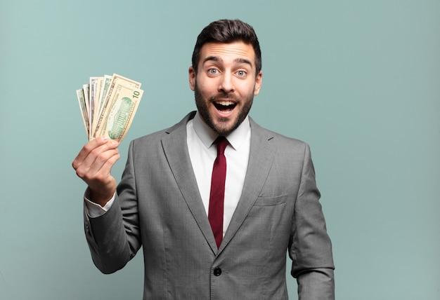 """Młody przystojny biznesmen wyglądający na bardzo zszokowanego lub zdziwionego, patrzący z otwartymi ustami i mówiący """"wow"""". koncepcja rachunków lub pieniędzy"""