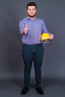 Młody przystojny biznesmen z nadwagą brodaty jako inżynier z kask na szaro