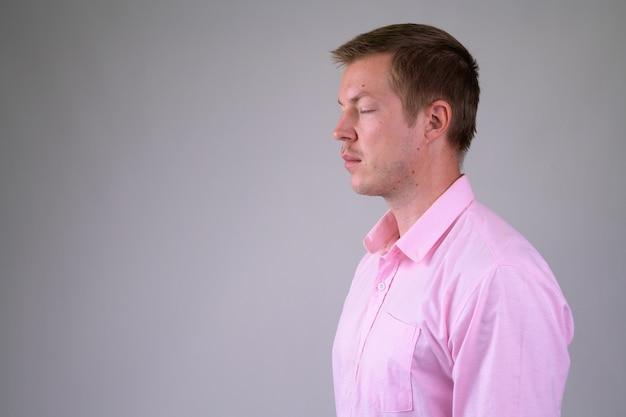 Młody przystojny biznesmen z różową koszulą