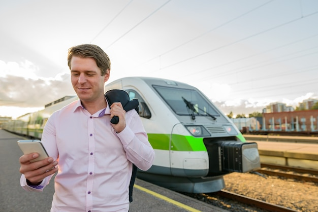 Młody przystojny biznesmen za pomocą telefonu komórkowego przed pociągiem na stacji kolejowej