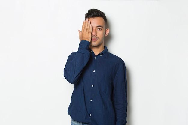 Młody przystojny biznesmen zakrywający jedno oko ręką na białym tle