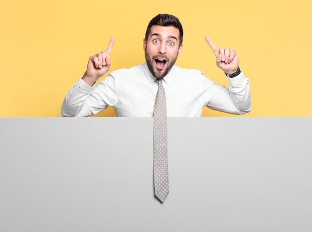 Młody przystojny biznesmen zdumiony, zaskoczony lub zszokowany wyrazem