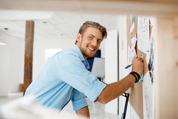 Młody przystojny biznesmena writing na papierze przyczepiającym corkboard.