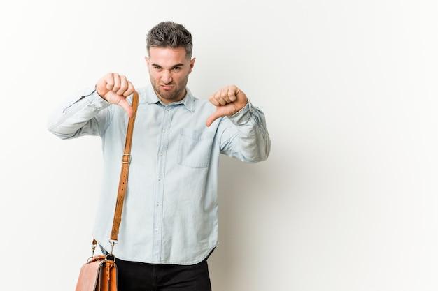 Młody przystojny biznesowy mężczyzna pokazuje kciuka puszek i wyraża niechęć.