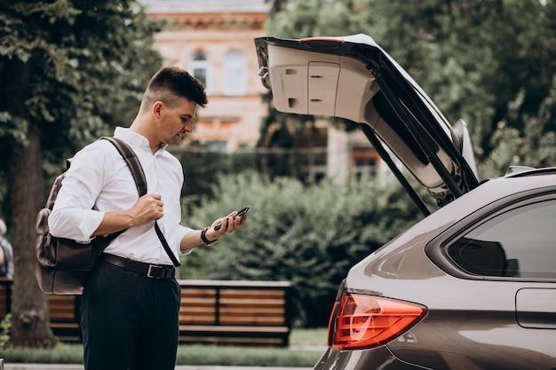 Młody przystojny biznesowy mężczyzna stojący samochodem z torbą podróżną