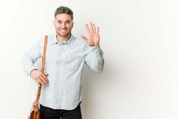 Młody przystojny biznesowy mężczyzna uśmiecha się rozochoconego seans liczba pięć z palcami.