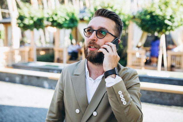 Młody przystojny biznesowy mężczyzna używa telefon
