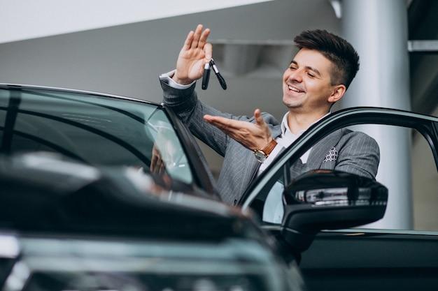 Młody przystojny biznesowy mężczyzna wybiera samochód w samochodowej sala wystawowej