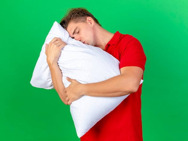 Młody przystojny blondyn chory przytulanie i całowanie poduszkę z zamkniętymi oczami na białym tle na zielonej ścianie