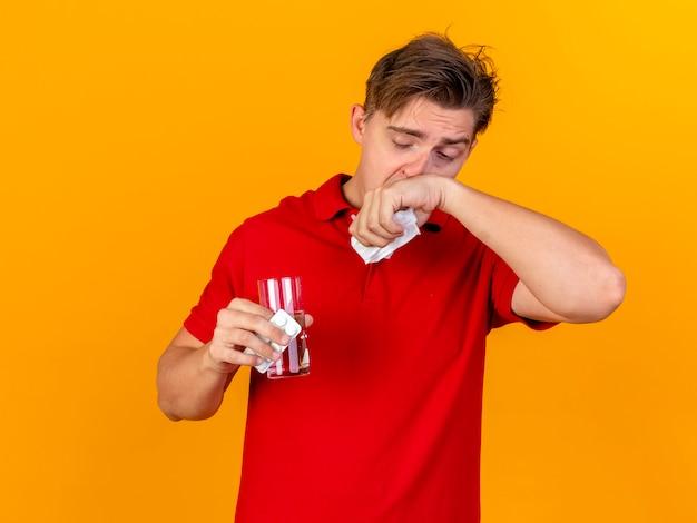 Młody przystojny blondyn chory trzyma opakowanie tabletek medycznych i szklankę wody z serwetką do wycierania nosa na białym tle na pomarańczowej ścianie