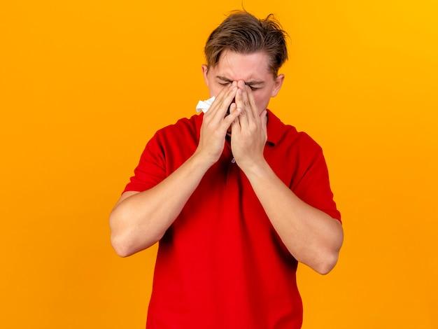 Młody przystojny blondyn chory trzymając serwetkę, trzymając ręce na twarzy z zamkniętymi oczami na pomarańczowej ścianie z miejsca na kopię
