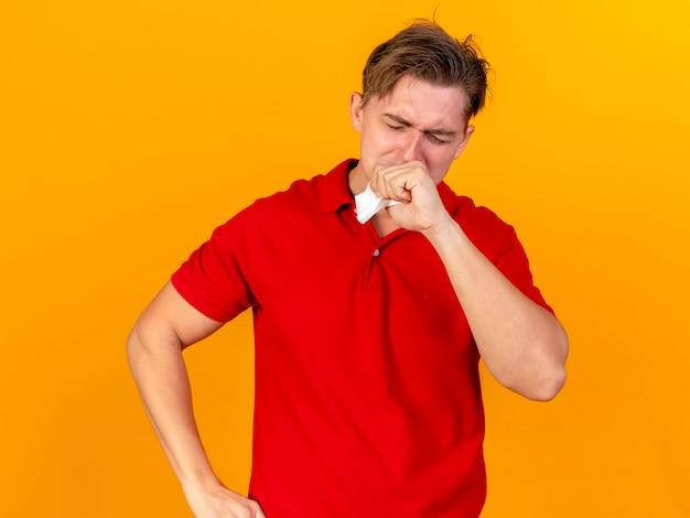 Młody przystojny blondyn chory trzymając serwetkę, trzymając rękę na ustach z zamkniętymi oczami na białym tle na pomarańczowej ścianie