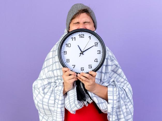 Młody przystojny blondyn chory ubrany w czapkę zimową i szalik owinięty w kratę, trzymając zegar z zamkniętymi oczami na fioletowej ścianie