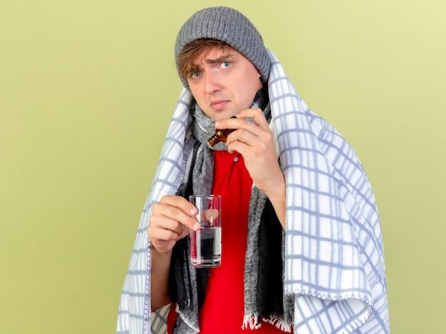 Młody przystojny blondyn chory ubrany w czapkę zimową i szalik zawinięty w kratę, wlewający lekarstwo do szklanki do szklanki wody, patrząc na kamerę odizolowaną na oliwkowym tle z miejscem na kopię